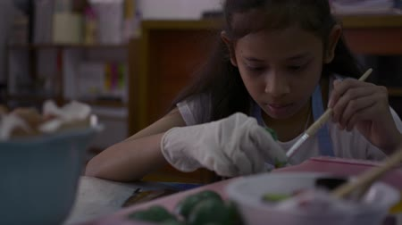 coisa : Asian cute girl is making crafts from egg shells on the desk, Young girl is coloring egg shells at home for her homework, Education concept.