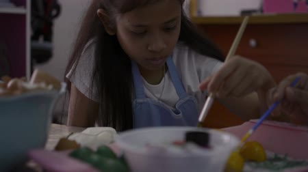 coisas : Asian girl and her mother are making crafts from the egg shells, Mother helping her daughter painting egg shells together at home, Education concept. Vídeos