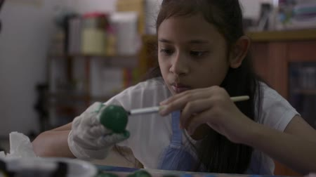 coisas : Asian cute girl is making crafts from egg shells on the desk, Young girl is coloring egg shells at home for her homework, Education concept.