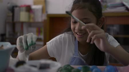 coloração : Asian cute girl is making crafts from egg shells on the desk, Young girl is coloring egg shells at home for her homework, Education concept.