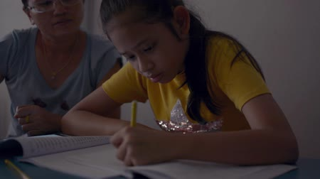 compreensão : Mother is using smart phone and teaching homework to her daughter on the desk, Education concept. Stock Footage
