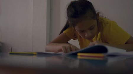 szándékozik : Cute girl in casual dress is doing homework intently on the desk, Education concept.