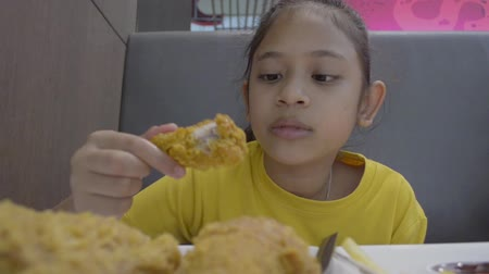 deep fried : Cute girl eating deep fried chicken in the restaurant during lunch.