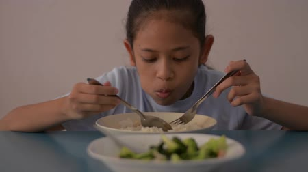 brócolis : Asian cute girl having lunch with stream rice and stir fried broccoli on the table, meal time with healthy food. Stock Footage