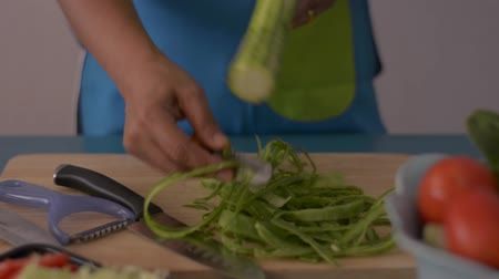 peeler : Close up shot of woman hands peeling angled loofah on wooden cutting board for healthy food on the table in the kitchen.
