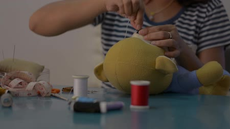 boneca : Woman sewing and fixing teddy bear doll on the desk at home, House work.