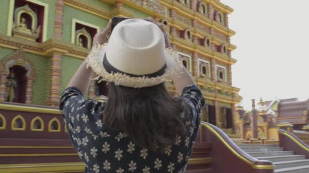 hayran olmak : Asian woman tourist taking pictures from mobile phone with a great pagoda in the buddhist temple. Stok Video