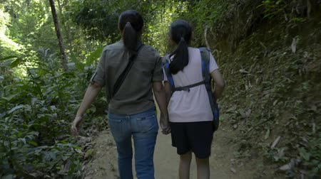 Rear view of mother and her daughter are walking hand in hand together on hiking trail along the stream that flowing from tropical rain forest in thailand.