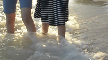 příloha : Asian girl with her sister walking hand in hand along together leisurely on the beach with waves washed up on the coast. low angle view shoot.