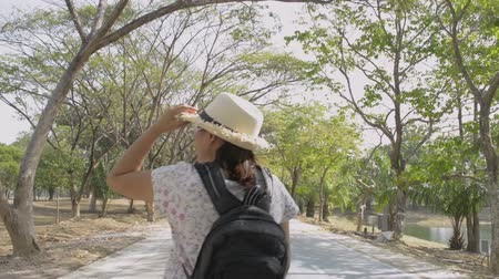 passeio público : Rear back view of asian woman with backpack and wearing straw hat is walking on the road in public park during summer.