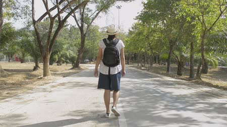 Rear back view of asian woman with backpack and wearing straw hat is walking on the road in public park during summer.