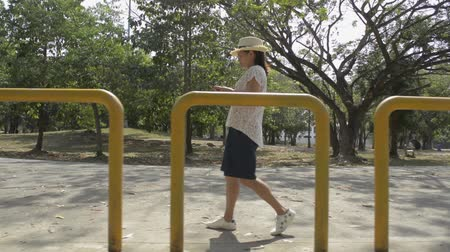 Asian woman in casual dress walking and using mobile phone in public park during summer.