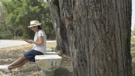 Asian woman in casual dress sitting under the tree and using mobile phone with social online in public park.