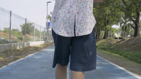 Rear back view of asian woman wearing straw hat is walking on the road in public park during summer. Vídeos