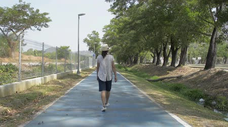 Rear back view of asian woman wearing straw hat is walking on the road in public park during summer. Stock Footage