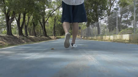 Low angle view from rear of woman legs walking on road in public park during summer.