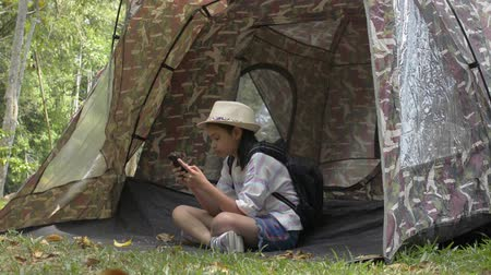 Asian cute girl with backpack sitting and using mobile phone in front of the tent in natural park area during camping.