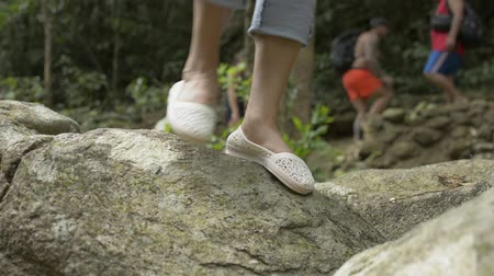 Close up woman legs walking over the rock in tropical jungle.