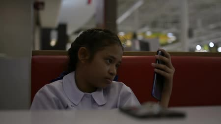 kafeterya : Asian cute schoolgirl sitting and using mobile phone in cafeteria after lunch.