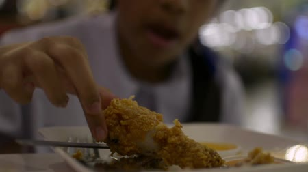 Cute schoolgirl eating deep fried chicken and french fried in cafeteria during lunch.