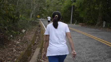 aim : Asian woman walking through the hill on the road. View from rear side of female people aiming to the mountain among tropical forest. Slow motion. Stock Footage