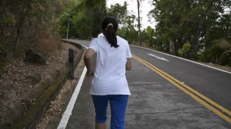 Asian woman running through the hill on the road. View from rear side of female runner aiming to the mountain among tropical forest. Slow motion.