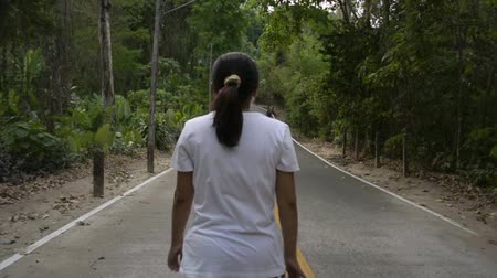 Asian woman walking through the hill on the road. View from rear side of female people aiming to the mountain among tropical forest. Slow motion. 動画素材