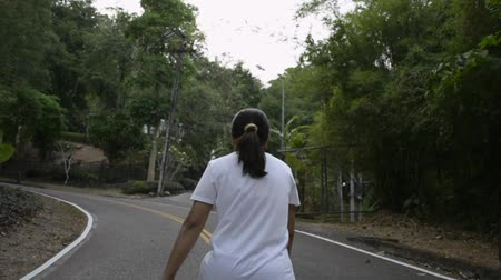 Asian woman walking through the hill on the road. View from rear side of female people aiming to the mountain among tropical forest. Slow motion. Stock Footage