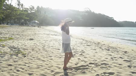 Asian cute girl wearing straw hat and casual dress standing on the beach under sunlight in the morning. Slow motion.