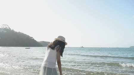 Asian cute girl wearing straw hat and casual dress standing and relaxing on the beach under sunlight in the morning. Slow motion. Stock Footage