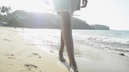 Asian girl wearing straw hat in casual dress with barefoot walking on the beach under sunlight. Low angle view with waves splashing on sandy beach. Slow motion. Stock Footage