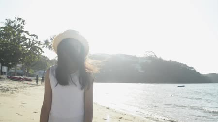 Asian cute girl wearing straw hat and casual dress walking on the beach under sunlight in the morning. Slow motion.