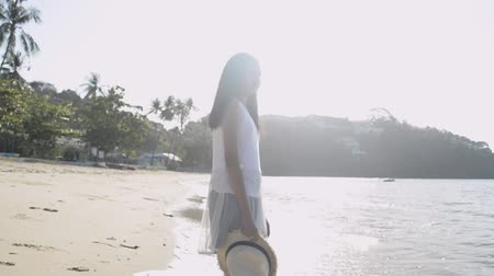 Asian cute girl holding straw hat wearing casual dress standing on the beach under sunlight in the morning. Slow motion. 動画素材