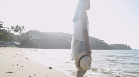 Asian cute girl holding straw hat wearing casual dress standing on the beach under sunlight in the morning. Slow motion. Stock Footage