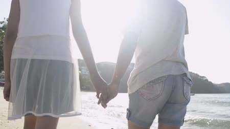 Mother and her daughter walking and holding hand in hand together happily on the beach under sunlight during summer. Expression of love. Slow motion. Stock Footage