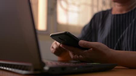 Close up woman hands using mobile smart phone on working desk for social online. Wireless technology concept.