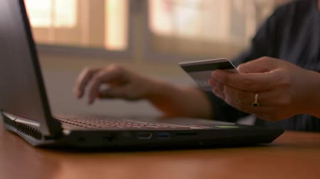 Hands of a woman holding a credit card and typing laptop keyboard for online payment on the desk at home.