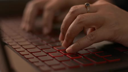 Close up of woman hands typing on a laptop computer keyboard, Office life.