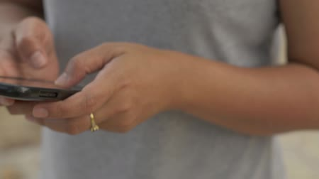 Close up woman hands texting message on mobile smart phone for communication and chatting on social online. Woman in casual dress using cell phone and walking in public park