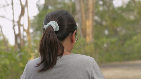 View from rear back of asian woman wearing eye glasses in casual dress using mobile phone and walking leisurely in natural park during summer. Close up follow shot from behind. Stock Footage