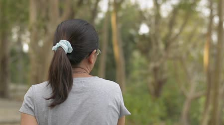 フォロー : View from rear back of asian woman wearing eye glasses in casual dress walking leisurely in natural park during summer. Close up follow shot from behind. Slow motion. 動画素材
