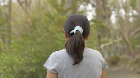 View from rear back of asian woman wearing eye glasses in casual dress walking leisurely in natural park during summer. Close up follow shot from behind. Stock Footage