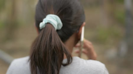 Close up and panning shot of asian woman from rear side wearing eyes glasses talking on the mobile phone in natural park. Slow motion.