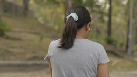 View from rear back of asian woman wearing eye glasses in casual dress walking leisurely in natural park during summer. Close up follow shot from behind. Slow motion. Stock Footage