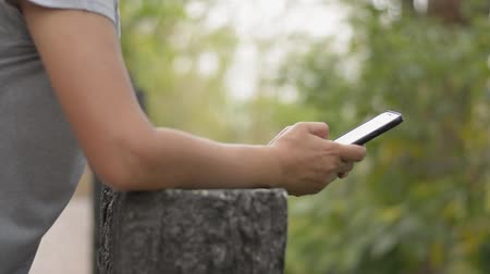 Close up panning shot of woman hands in casual dress texting message on mobile smart phone for communication and chatting on social online. Using cell phone at beautiful natural park under sunlight. Wireless technology and Environment concept. Stock Footage