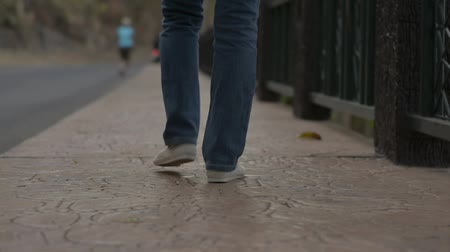 View from rear side of asian woman legs wearing jeans walking leisurely on the footpath along the road in the evening. Close up follow shot with low angle view. Slow motion. Stock Footage