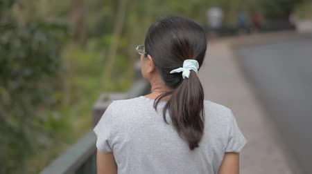 フォロー : View from rear side of asian woman wearing eye glasses in casual dress walking leisurely on the footpath along the road in the evening. 動画素材