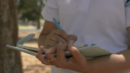 Woman walking and writing to inspire life on diary in public park during summer. Outdoor work recording. Slow motion. Stock Footage