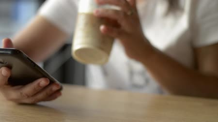 Asian woman using and texting message on mobile smart phone for communication and chatting on social online during drinking a cup of cold drink in coffee shop.
