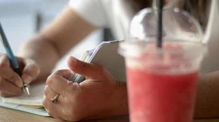 книжный магазин : Asian woman sitting and writing on diary to inspire life in the drink shop with a cup of smoothie fruit juice on the table.